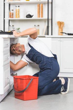 Photo pour Réparateur adulte avec seau rouge vérifier les tuyaux de l'évier à la cuisine - image libre de droit