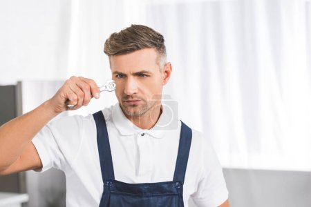 thoughtful adult repairman holding and looking at wrench with screw