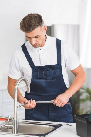adult repairman holding pipe while repairing faucet at kitchen