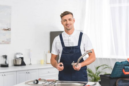 smiling adult repairman taking off kitchen faucet for repairing and looking at camera