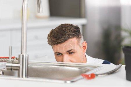 Photo pour Vue recadrée du réparateur adulte regardant évier à la cuisine - image libre de droit