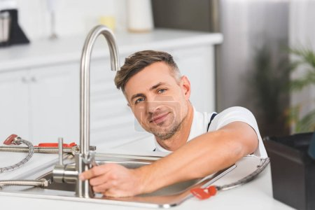 smiling adult repairman with spanner repairing faucet at kitchen and looking at camera