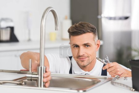 smiling adult repairman holding pipe and spanner while repairing faucet at kitchen and looking at camera
