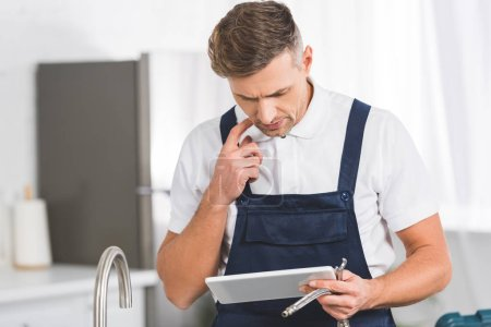 thoughtful adult repairman holding tools and looking at digital tablet while repairing kitchen faucet