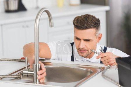 Photo pour Réparateur adulte tenant le tuyau et la clé pendant la réparation du robinet à la cuisine - image libre de droit