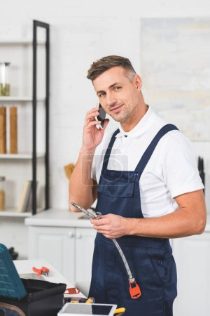smiling adult repairman holding pipe for kitchen faucet repairing and looking at camera while talking on smartphone