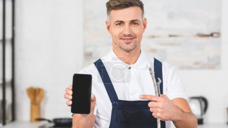 smiling adult handyman holding pipe and pointing at smartphone with blank screen