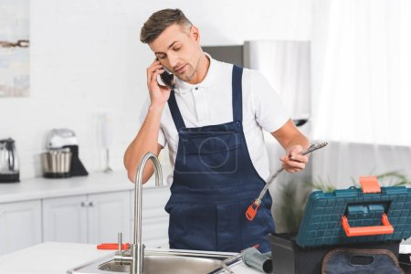 adult repairman holding pipe and talking on smartphone while repairing kitchen faucet