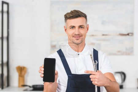 Photo for Smiling adult man holding pipe and spanner while pointing at smartphone wit blank screen - Royalty Free Image