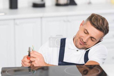 Photo pour Réparateur adulte parler sur smartphone lors de réparation électrique poêle à cuisine - image libre de droit