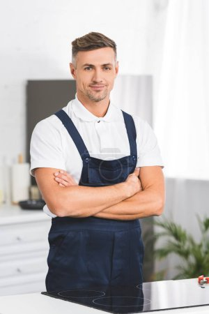 adult repairman standing near electric stove with crossed arms at kitchen and looking at camera