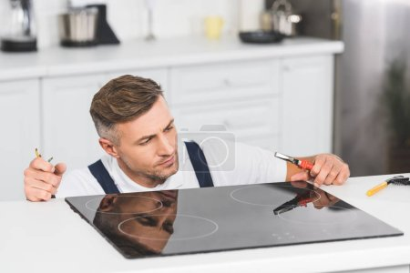 thoughtful adult repairman repairing electric stove at kitchen