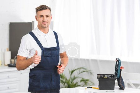 Photo for Adult repairman holding screwdriver and showing thumb up sign at kitchen and looking at camera - Royalty Free Image