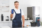 smiling adult repairman showing smartphone with Facebook app while standing at kitchen and looking at camera