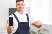 smiling adult repairman holding smartphone and pointing with finger at blank screen and looking at camera