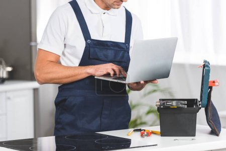 cropped view of adult repairman using laptop while repairing electric stove at kitchen