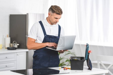 thoughtful adult repairman using laptop while repairing electric stove at kitchen