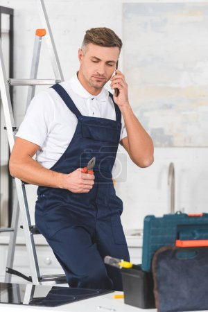 adult repairman sitting on ladder, holding pliers and talking on smartphone at kitchen
