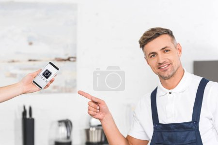 partial view of hand holding smartphone and smiling adult repairman pointing with finger at screen with uber app