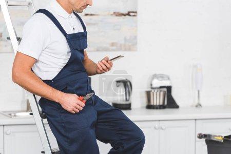 Photo pour Recadrée vue du réparateur assis sur échelle tenant une pince et en utilisant le smartphone à la cuisine - image libre de droit