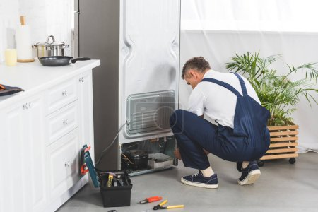 adult handyman repairing refrigerator at kitchen with tools on floor