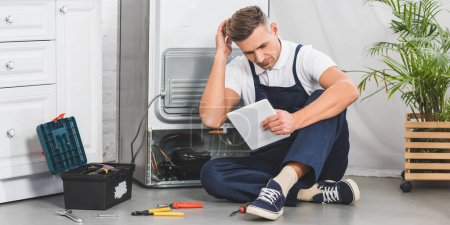 Photo for Thoughtful adult repairman sitting on floor and using digital tablet while repairing refrigerator - Royalty Free Image