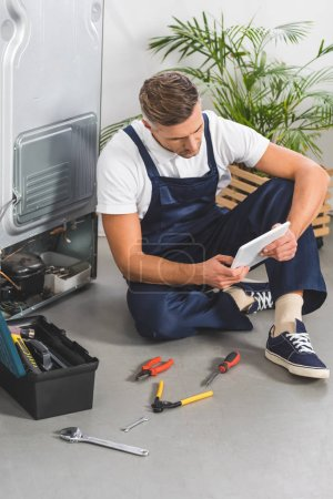 Photo for Adult repairman sitting on floor and using digital tablet while repairing refrigerator - Royalty Free Image