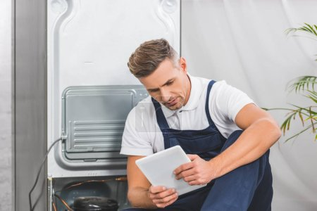 adult repairman sitting on floor and using digital tablet while repairing refrigerator