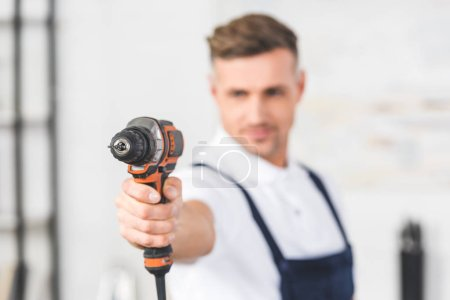 selective focus of adult repairman holding drill in hand