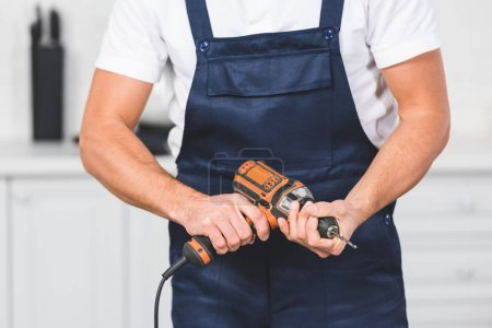 cropped view of repairman holding drill inhands