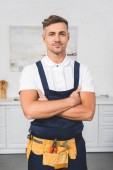 adult repairman in tool belt standing with crossed arms at kitchen and looking at camera