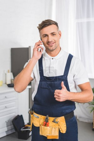 adult repairman in tool belt talking on smartphone and showing thumb up sign
