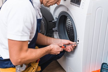 cropped view of adult repairman working with screwdriver while repairing washing machine in bathroom