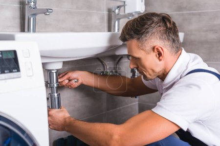 Photo for Adult plumber fixing sink at bathroom - Royalty Free Image