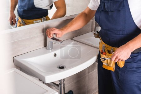 cropped view of repairman checking faucet after repairing and holding spanner