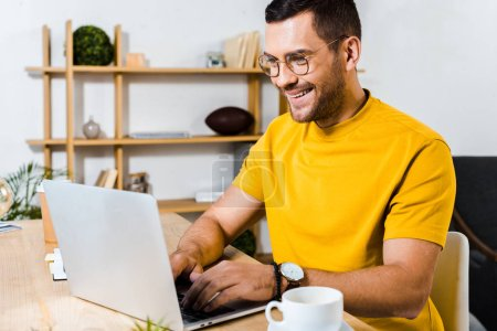 Photo for Handsome man smiling while using laptop - Royalty Free Image