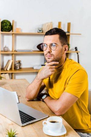 hombre pensativo sentado en vasos cerca de la computadora portátil y una taza de café
