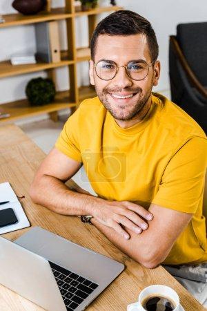 Photo pour Homme souriant assis dans des lunettes près d'un ordinateur portable et une tasse de café - image libre de droit