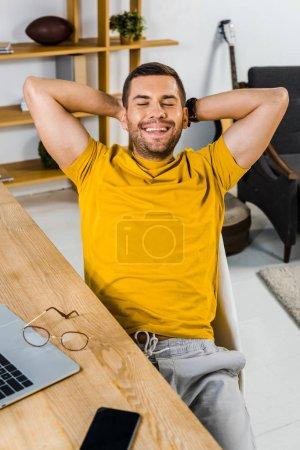 homme joyeux assis sur une chaise et souriant à la maison