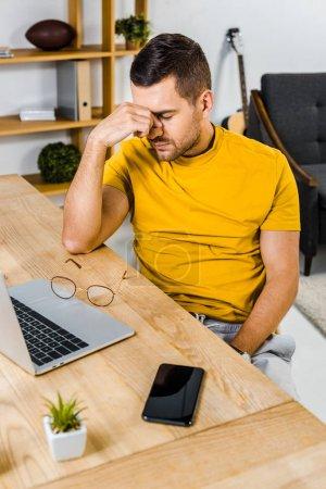 Photo pour Homme fatigué, assis près d'ordinateur portable et le smartphone à la maison - image libre de droit