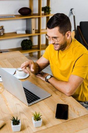 Photo pour Homme joyeux pointant du doigt à l'ordinateur portable à la maison - image libre de droit