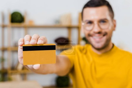selective focus of credit card in hand of cheerful man