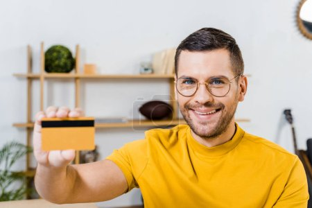 Photo for Close up of smiling man holding credit card in hand - Royalty Free Image