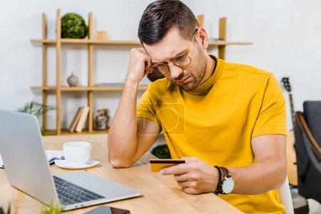 Foto de Hombre molesto en gafas mirando a la tarjeta de crédito en casa - Imagen libre de derechos