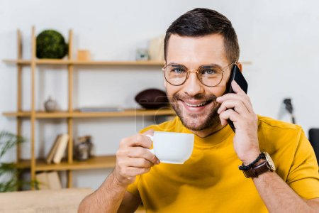 Photo for Handsome man talking on smartphone while holding cup of coffee - Royalty Free Image