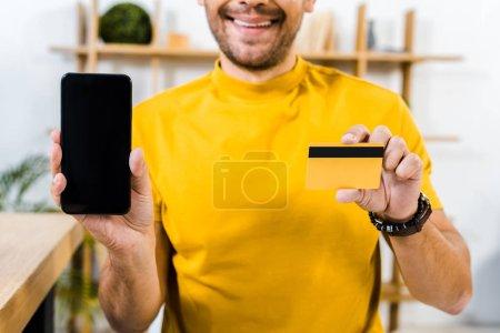 Foto de Recorta la vista del hombre que sostiene el smartphone con la pantalla en blanco y tarjeta de crédito en las manos - Imagen libre de derechos