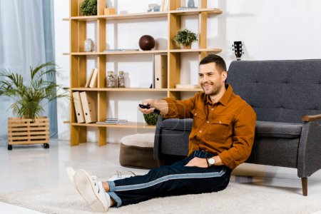 cheerful man holding remote control and sitting on floor in modern living room