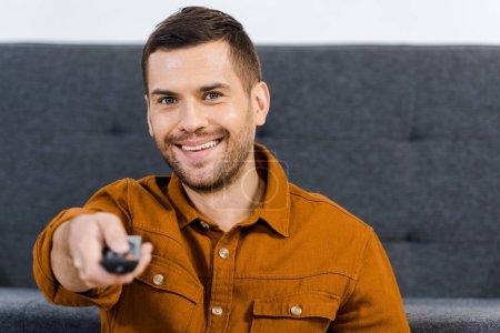 Photo pour Foyer sélectif de l'homme joyeux tenant la télécommande à la maison - image libre de droit