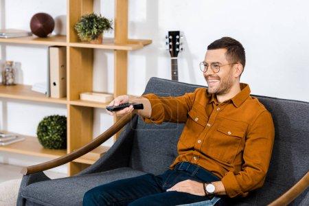 Photo pour Bel homme assis sur le canapé et la tenue de télécommande - image libre de droit