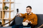 handsome man sitting on sofa with popcorn in bowl and holding remote control